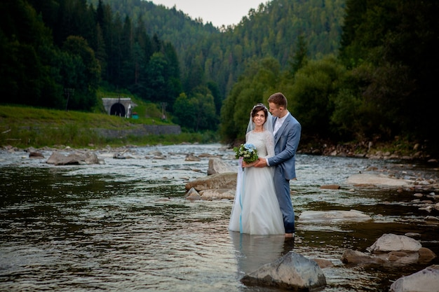 Happy newlyweds standing and smiling on the river
