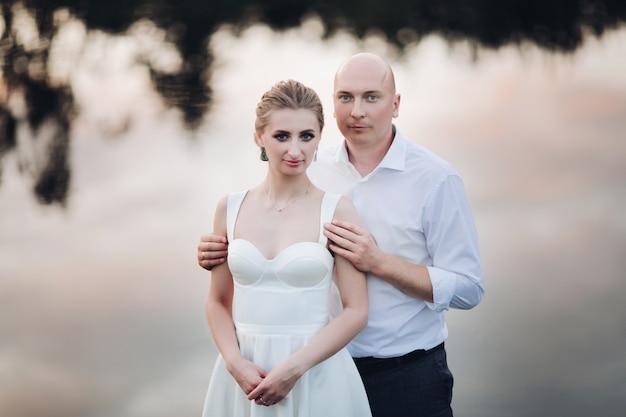 幸せな新婚夫婦は湖の近くでたくさんの結婚式の写真を撮ります
