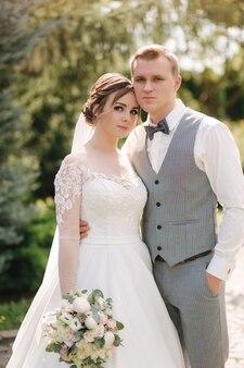 Счастливые молодожены гуляют на свежем воздухе в день свадьбы. жених и невеста проводят время вместе