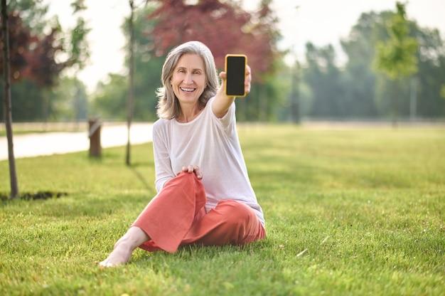 Радостные новости. радостная приветливая женщина пенсионного возраста в брюках и джемпере босиком показывает экран смартфона, сидя на зеленой лужайке в парке