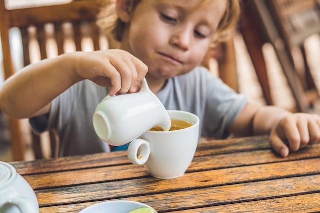Happy nice boy pours honey into the tea in summer green garden