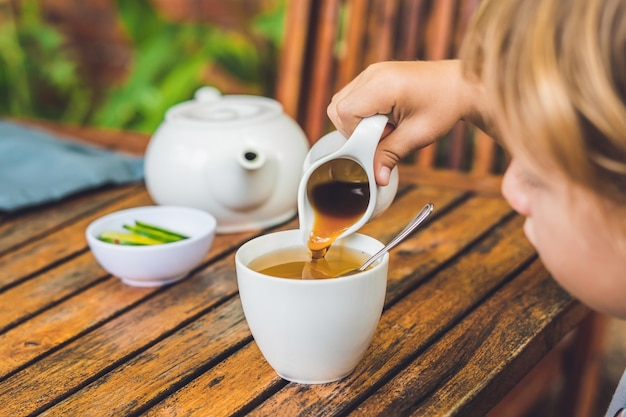 Happy nice boy pours honey into the tea in summer green garden