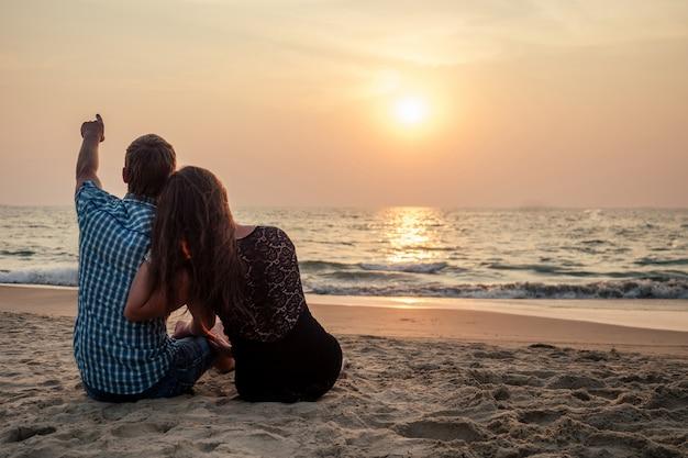 Счастливая милая пара, наблюдая закат море