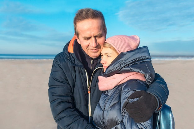 Happy nice elderly senior mature married couple in love walking, enjoying  together on the winter beach, gulf. retired handsome man, husband is hugging his beautiful wife outdoors. love lives forever.