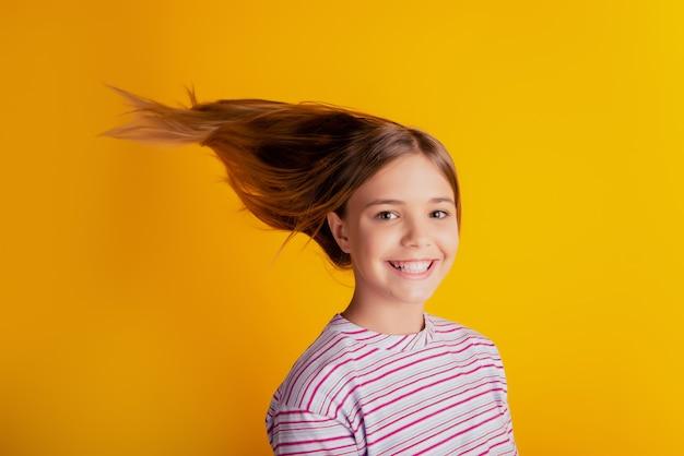 Счастливая милая маленькая девочка со светлыми волосами, летящими на желтом фоне