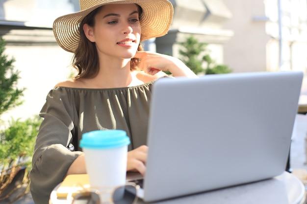 Счастливая милая женщина, работающая на ноутбуке в уличном кафе.
