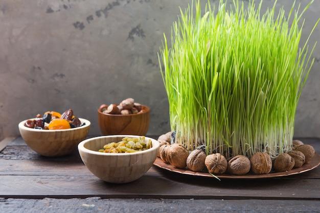 해피 nowruz 휴일 벽. 녹색 잔디 밀, 복사 공간 평면도와 다양한 말린 과일, 견과류, 씨앗, 가벼운 벽을 축하