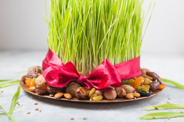 Happy nowruz holiday wall. celebrating  various dried fruits, nuts, seeds, light wall with green grass wheat, copy space top view