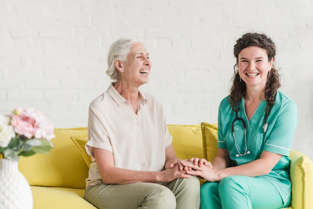 Happy nurse and senior woman sitting on sofa holding hands