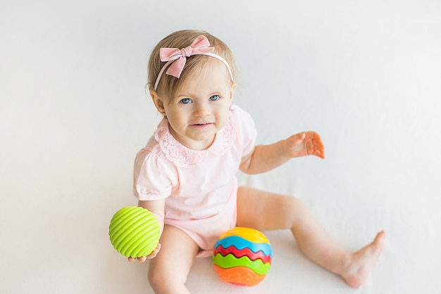 Happy nursery baby girl playing with colorful rubber ball at home