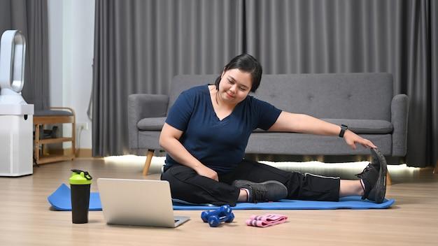 행복한 비만 여성은 집에서 노트북 컴퓨터로 요가를 연습합니다. 건강과 체중 개념을 잃고 싶어.