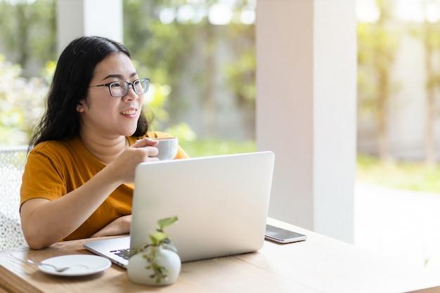 Счастливый азиатских внештатных людей бизнес-леди, работающая с портативным компьютером и держащая кофе и смартфон в кафе, как