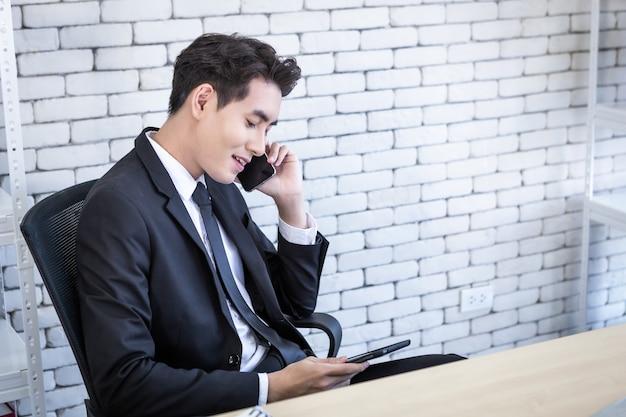 アジアの青年実業家の幸せは、白い壁のオフィスの背景に白い木製のテーブルでテーブルを操作してスマートフォンをピックアップします