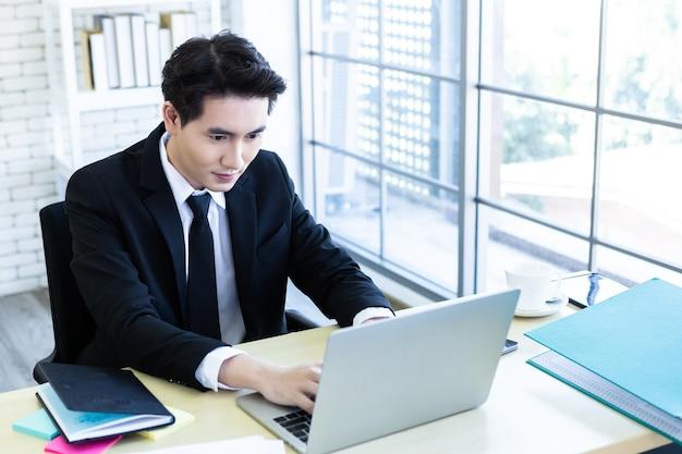 Счастливый азиатский молодой бизнесмен видит успешный бизнес-план на портативном компьютере и ручке на фоне деревянного стола в офисе, бизнес выражает уверенность в себе