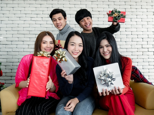 Счастливый группы молодых азиатских с подарками дома в праздновании рождественского фестиваля. группа друзей, наряжающихся для рождественской вечеринки вместе. празднование нового года. веселого рождества и счастливых праздников.