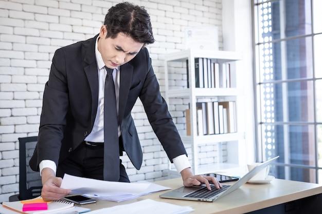 성공적인 아시아 젊은 사업가의 행복은 사무실 배경에서 목탁에 있는 문서 사업 계획과 노트북 컴퓨터를 보도록 강조했습니다.