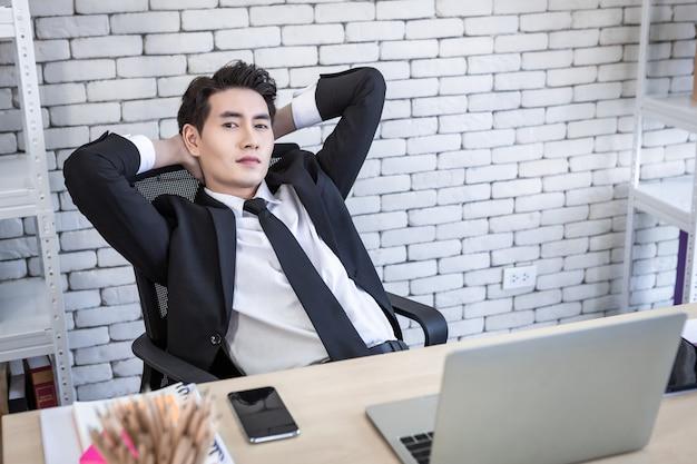 사무실 배경에서 노트북 컴퓨터, 스마트폰, 연필로 성공한 아시아 젊은 사업가의 행복.
