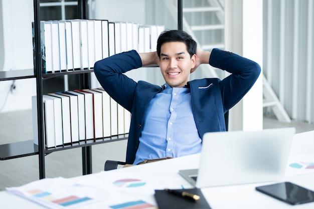 노트북 컴퓨터, 빈 터치 스크린이 분리된 태블릿, 사무실의 흰색 나무 테이블 배경에 있는 노트북에 있는 성공적인 아시아 젊은 사업가의 행복