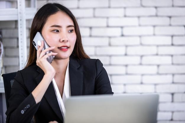 성공적인 아시아 젊은 여성 사업가가 흰 벽 사무실 배경의 흰색 나무 테이블에서 노트북 컴퓨터로 작업하는 스마트폰을 들고 있는 것을 기뻐합니다.