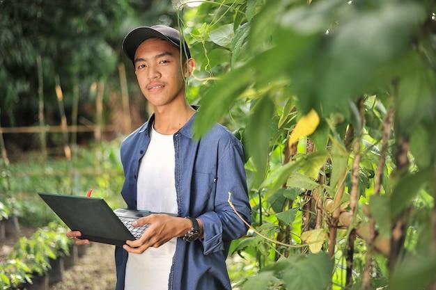 ノートパソコンを使用して長い豆の品質をチェックするときに笑顔の若いアジアの農家の男性の幸せ