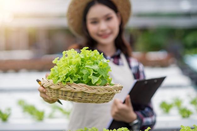 Счастливый молодой азиатской женщины на овощной ферме