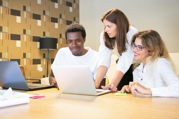 Colleghi di ufficio felici che guardano insieme la presentazione del progetto