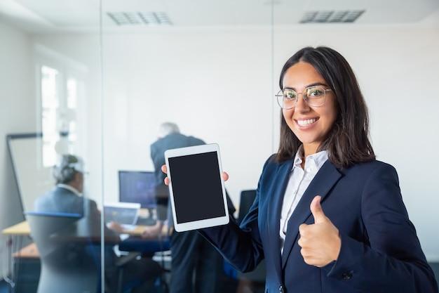 행복 한 사무실 아가씨 빈 태블릿 화면을 보여주는 제스처처럼 만들고, 카메라를보고 웃 고. 공간을 복사하십시오. 커뮤니케이션 및 광고 개념