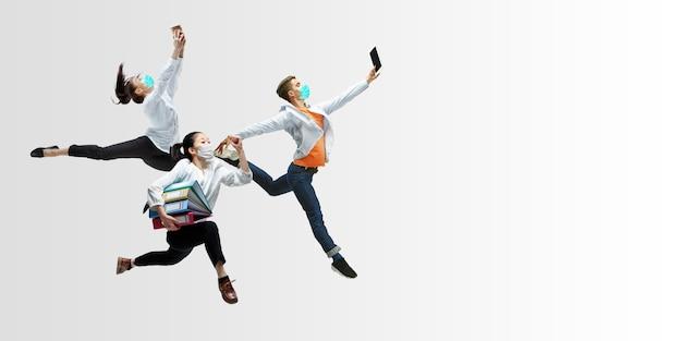 Счастливые офисные работники в масках прыгают и танцуют в повседневной одежде или костюме, изолированном на фоне студии. бизнес, запуск, профилактика covid, концепция движения и действий. творческий коллаж.