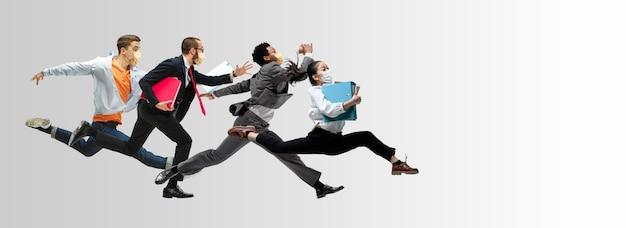 얼굴 마스크를 쓴 행복한 사무실 직원들은 캐주얼 옷이나 고립된 양복을 입고 점프하고 춤을 춥니다.
