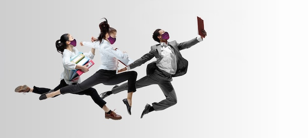 Счастливые офисные работники в масках прыгают и танцуют в повседневной одежде