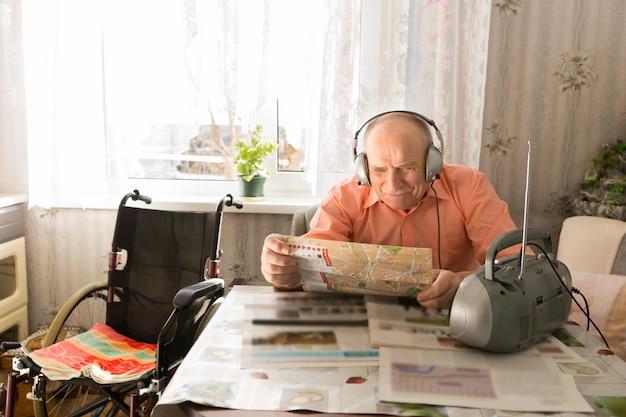 幸せな老禿げた男、リビングルームに座って、ヘッドセットでラジオを聴きながら新聞を読む