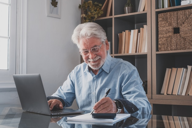 Happy old caucasian businessman smiling working online watching webinar podcast on laptop and learning education course conference calling make notes sit at work desk, elearning concept