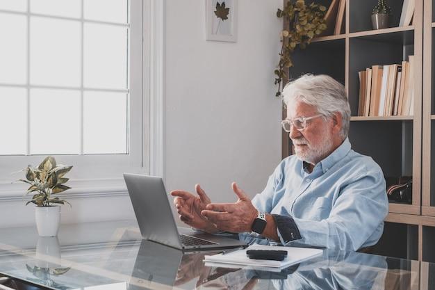 Счастливый старый кавказский бизнесмен улыбается, работает онлайн, смотрит подкаст веб-семинара на ноутбуке и изучает образовательный курс, конференц-связь, делает заметки, сидя за рабочим столом, концепция электронного обучения
