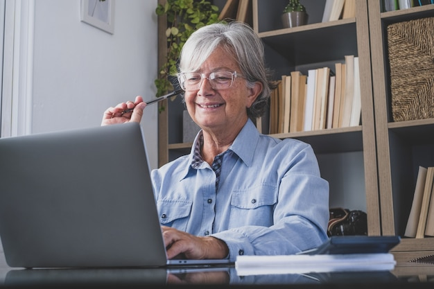 Happy old caucasian businesswoman smiling working online watching webinar podcast on laptop and learning education course conference calling make notes sit at work desk, elearning concept