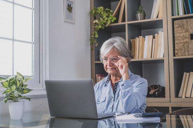 행복한 노년의 백인 여성 사업가가 노트북으로 온라인 웨비나 팟캐스트를 시청하고 교육 과정 회의 통화를 하며 메모를 업무용 책상에 앉히고 전자 학습 개념
