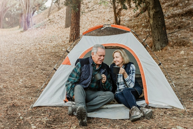 Happy old couple having coffee by the tent in the forest
