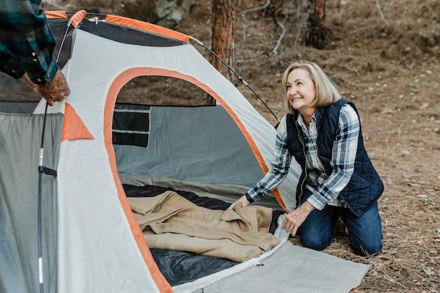 Счастливая пожилая пара, устанавливающая палатку в лесу