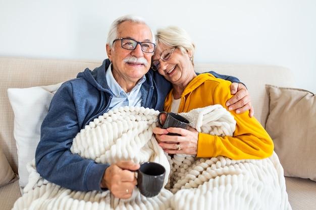 ソファに座って幸せな老夫婦。居心地の良い、コーヒーやお茶を飲む