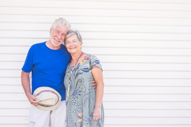 화창한 날에 손에 모자와 함께 웃 고 행복 한 오래 된 커플