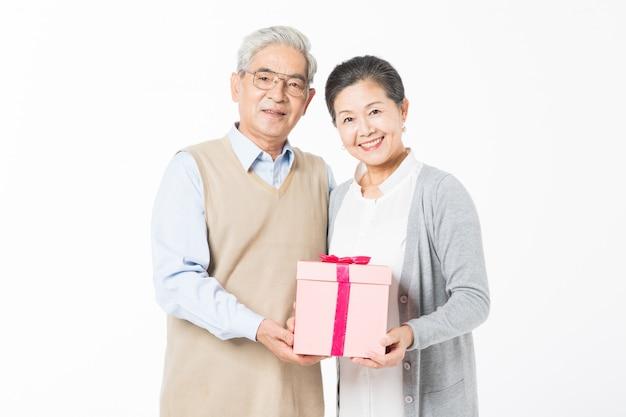 Счастливые старые пары с подарочными коробками