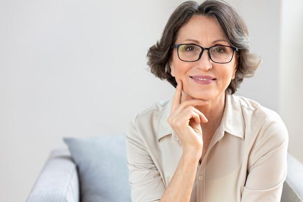 Счастливая старая женщина в очках, сидя на софе у себя дома или в офисе. портрет улыбающейся зрелой женщины средних лет, смотрящей в камеру