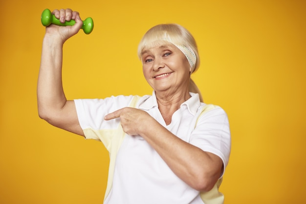 Happy old lady doing bicep dumbbells exercise