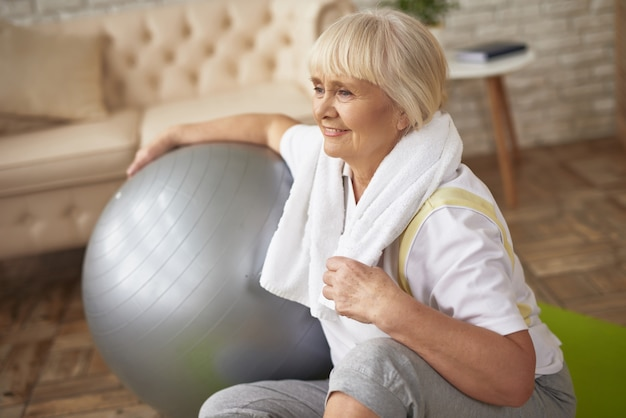Happy old lady with fit ball workout recovery.