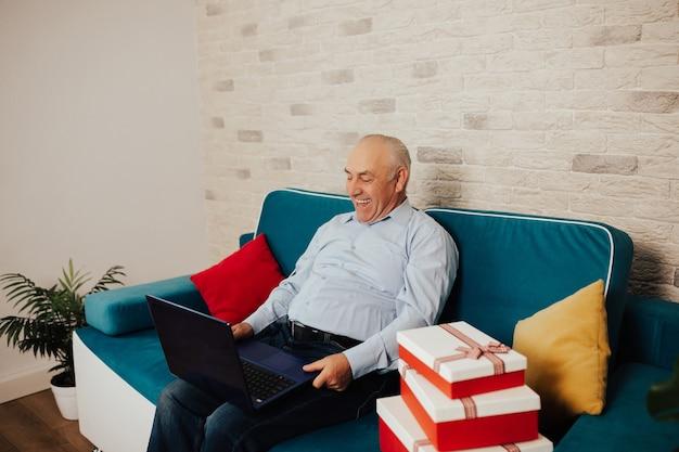 스마트 캐주얼 스타일을 입은 행복한 노인은 노트북을 사용하고 휴가 기간 동안 집에서 소파에 앉아 웃고 있습니다.