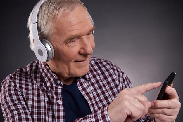 Happy old man in headphones chooses music on phone.