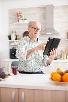 タブレットpcを使用してbreakfat中にキッチンで幸せな老人。モバイルアプリ、タッチスクリーンを備えた最新のインターネットオンライン情報技術を使用して定年のタブレットポータブルパッドpcを持つ高齢者