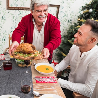 Happy old man putting roasted chicken on festive table
