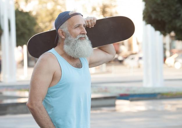 행복한 노인. 삶의 만족의 개념. 스케이트 보드와 함께 긍정적 인 회색 머리 남자의 초상화. 우승자 개념.