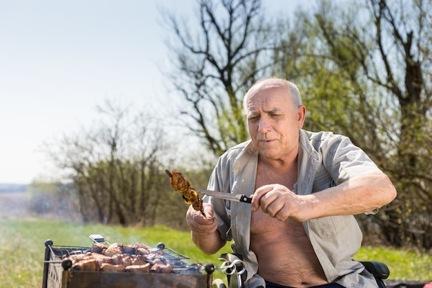 셔츠를 입은 행복한 노인이 휠체어에 앉아 칼을 사용하여 막대기에 구운 고기가 제대로 익었는지 확인합니다.