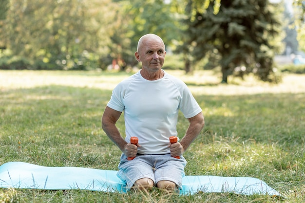 Happy old man working out in nature